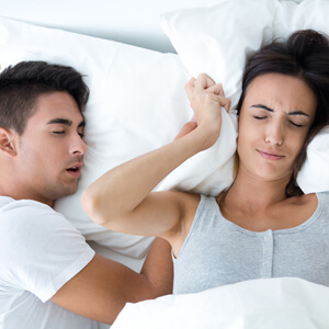 Woman with pillow over ears next to snoring partner